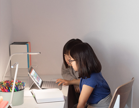 image of 2 children working on a laptop in a home study