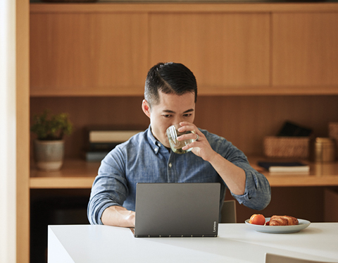 image of a man sipping coffee and working on a laptop